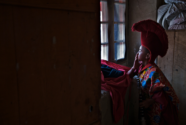 a-young-monk-watches-the-masked-dance-festival-at-phyang-monastery-from-the-changing-room-as-he-awaits-his-turn-to-perform-ladakh-india