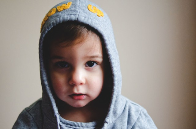 Image of toddler boy with gray hooded sweatshirt, face partially lit and partially shadowed.