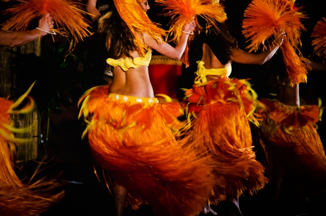 """Movement"" by Jen Hooks, a photo of hula dancers with vibrant orange swaying skirts and shaking pom-poms."