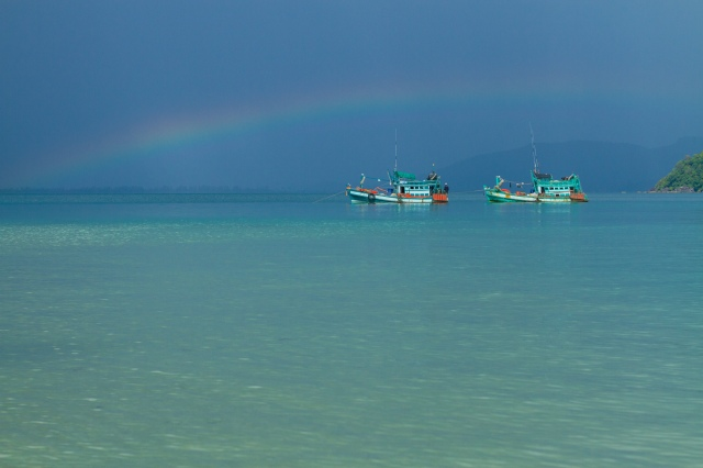 A rainbow arcs over boats in the Bay of Thailand.