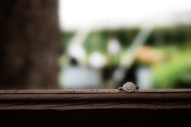 An image of an engagement ring sitting on a wooden ledge.