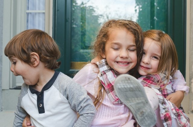 "A photo of three young kids, one looking away from the camera, one with eyes closed, and one embracing another, with a foot in front of the camera. By <a href=""http://threebirds.blog"" target=""new"">Jen Hooks</a>"