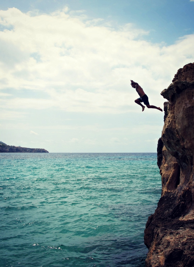 Vertical shot of a man jumping off a cliff at Cala Tarida on Ibiza by Cheri Lucas Rowlands.