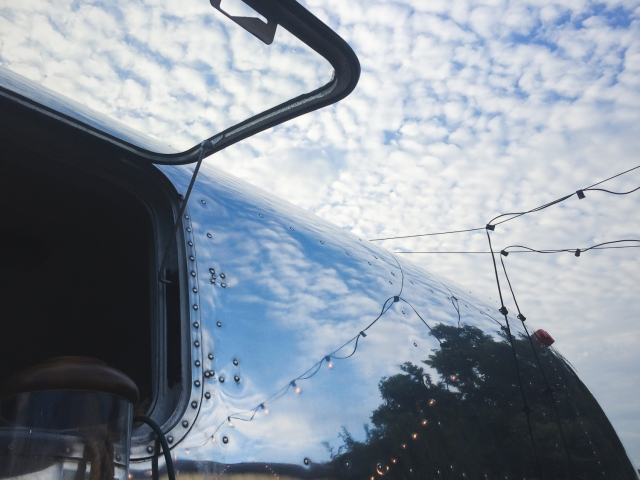 "Mirror, by <a href=""http://threebirds.blog"">Jen Hooks</a>, a morning sky reflected in an Airstream, which is also a coffee shop."