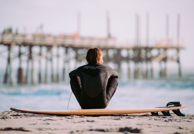 A photo of a surfer sitting on a surfboard on the beach